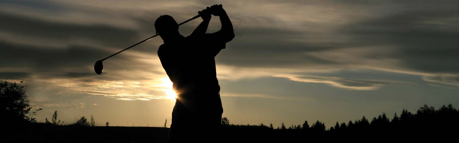 Golfer swing a club at dusk